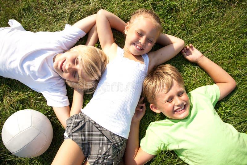 Kinder auf Gras lizenzfreie stockbilder