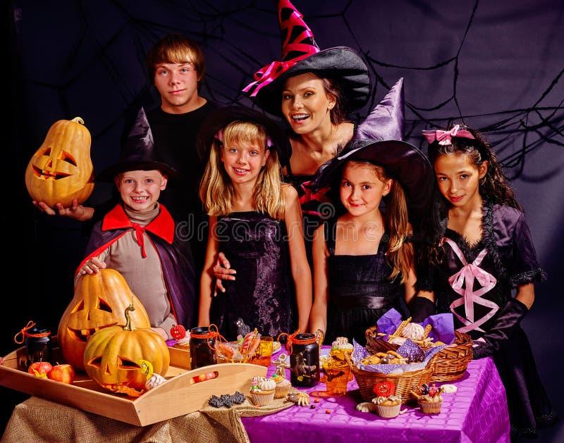 Kinder auf Halloween-Partei, die Kürbis mit Erwachsenem macht stockfotografie