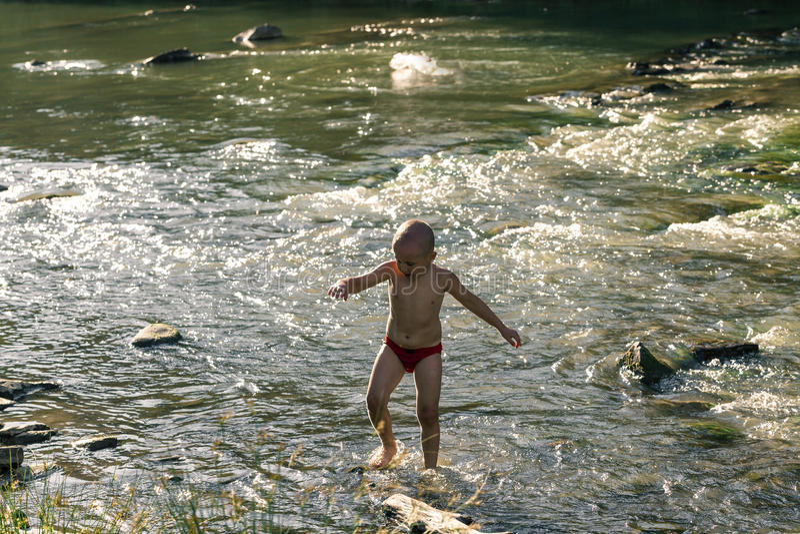 Kinder baden in einem Gebirgsfluss stockbild