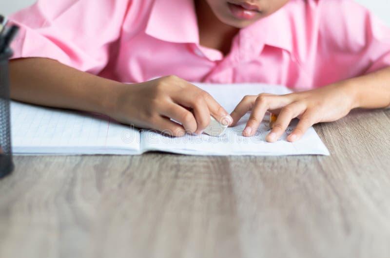Kinder benutzen einen Radiergummi löscht Wort stockfoto