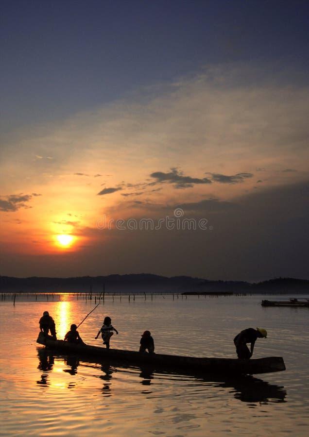 Kinder am Boot auf Sonnenuntergang stockfotografie