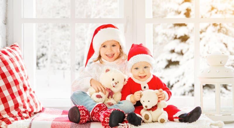 Kinder Bruder und Schwester, die auf dem Winterfenster Weihnachten lachen und sitzen stockfotografie