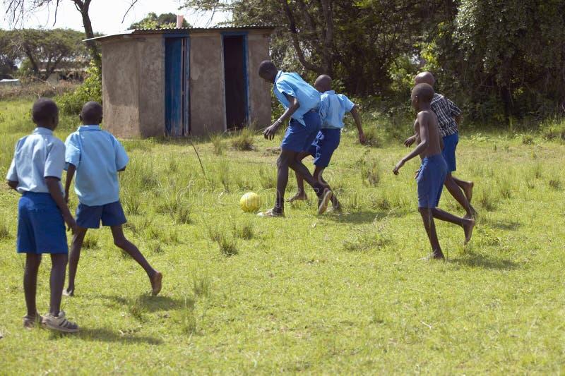 Kinder in den blauen Uniformen, die in der Schule Fußball nahe Nationalpark Tsavo, Kenia, Afrika spielen stockbild