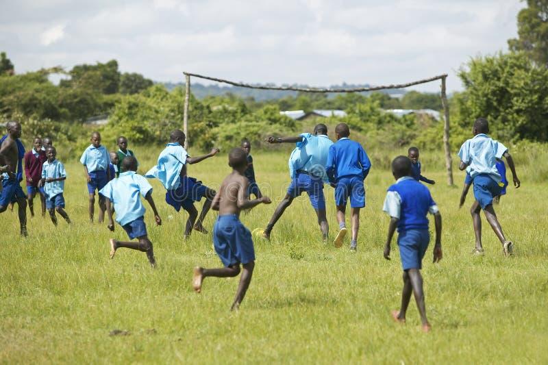 Kinder in den blauen Uniformen, die in der Schule Fußball nahe Nationalpark Tsavo, Kenia, Afrika spielen lizenzfreie stockfotos