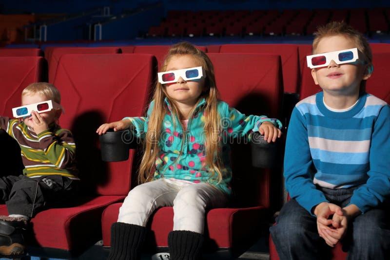 Kinder in den Gläsern 3D einen Film aufpassend stockbilder