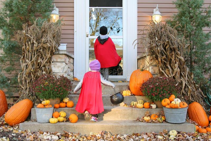 Kinder in den Kap-Kostümen, die auf Halloween Trick-oder-behandeln lizenzfreie stockfotografie