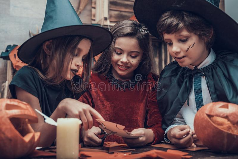 Kinder in den Kostümen, die Halloween-Dekorationen machen stockfotografie
