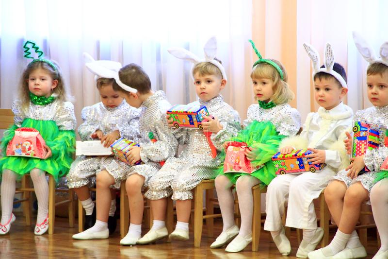 Kinder in den Kostümhasen sitzen auf Matinee im Kindergarten für neues Jahr stockfotografie