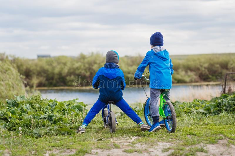 Kinder in den Mänteln und in den Hüten auf Fahrrädern auf den Banken des Flusses stockbilder