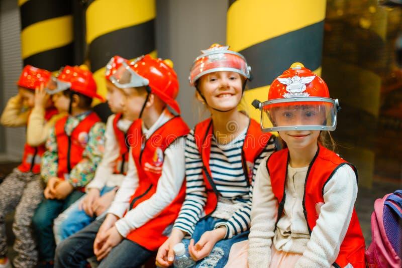 Kinder in den Sturzhelmen und Uniform, die Feuerwehrmann spielt stockfoto