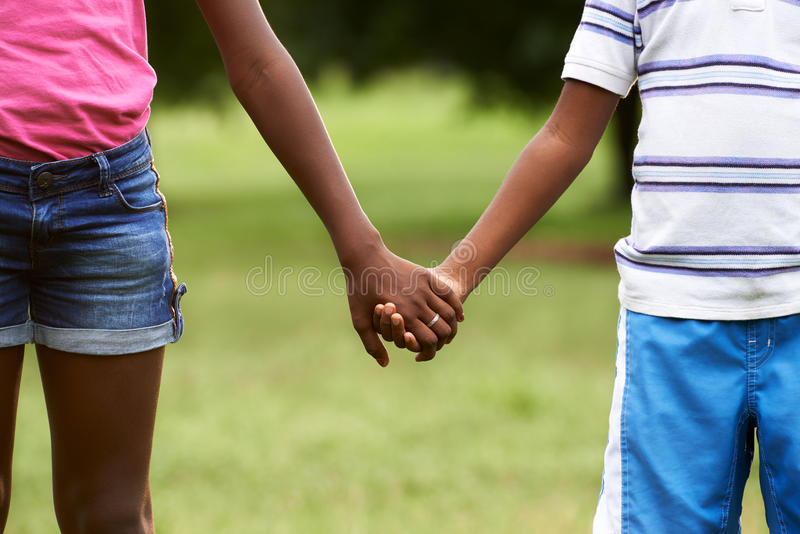 Kinder in der Liebe schwärzen Jungen- und Mädchenhändchenhalten stockbild