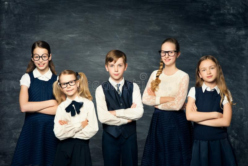 Kinder in der Schuluniform über Tafel, Kinderstudenten-Porträt auf schwarzem Hintergrund stockfotos