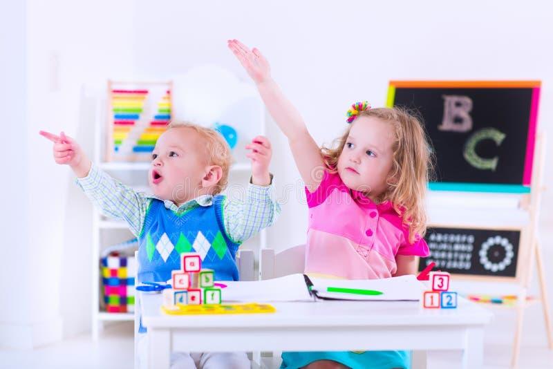 Kinder an der Vorschule Zwei Kinder, die am Kindergarten zeichnen lizenzfreie stockbilder