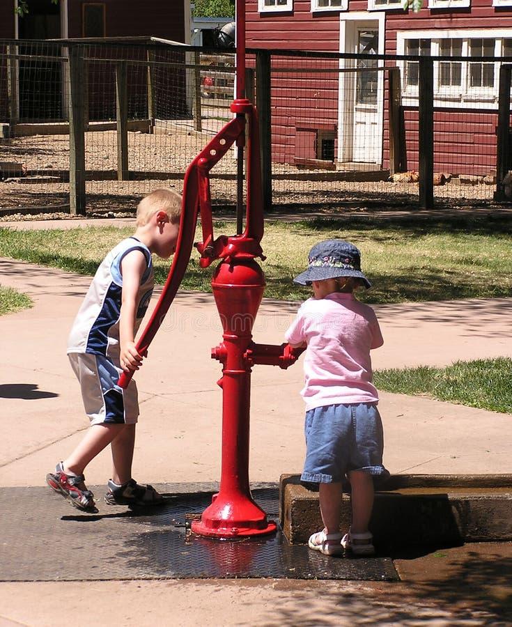 Kinder an der Wasser-Pumpe stockfoto