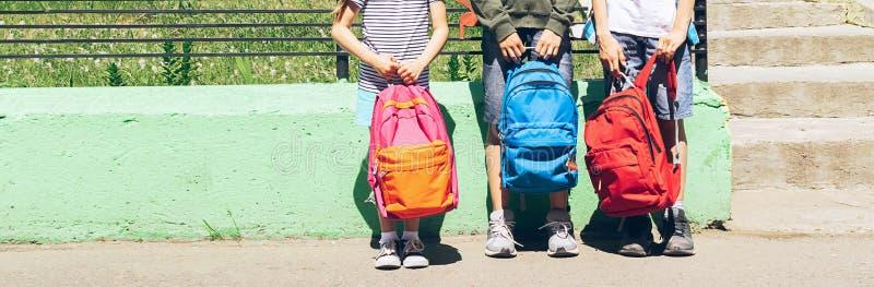 Kinder des unterschiedlichen Alters, der Jungen und der Mädchen halten helle Rucksäcke Auf schwarzem Hintergrund mit copyspace Ho stockfotos
