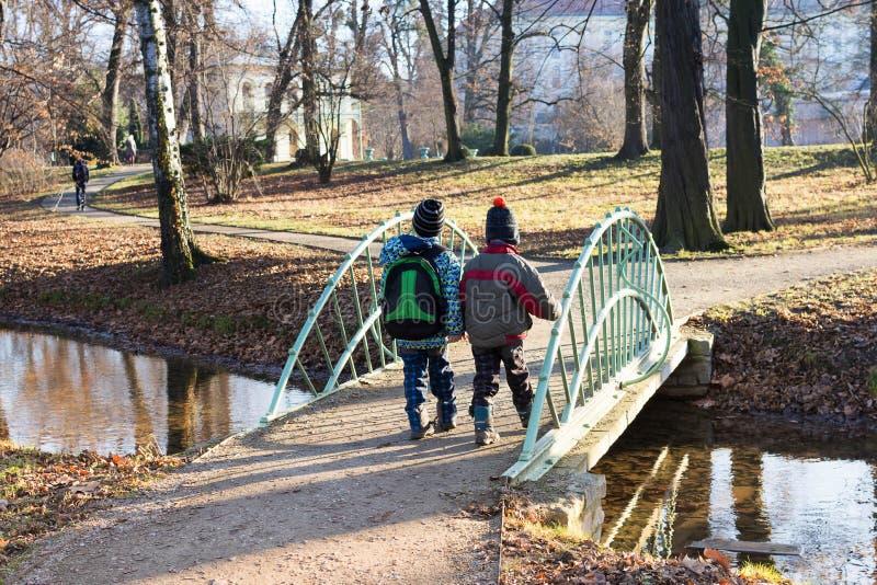 Kinder, die über Brücke im Park gehen stockfotos