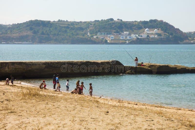 Kinder, die an Alges-Strand in Lissabon spielen lizenzfreie stockfotografie