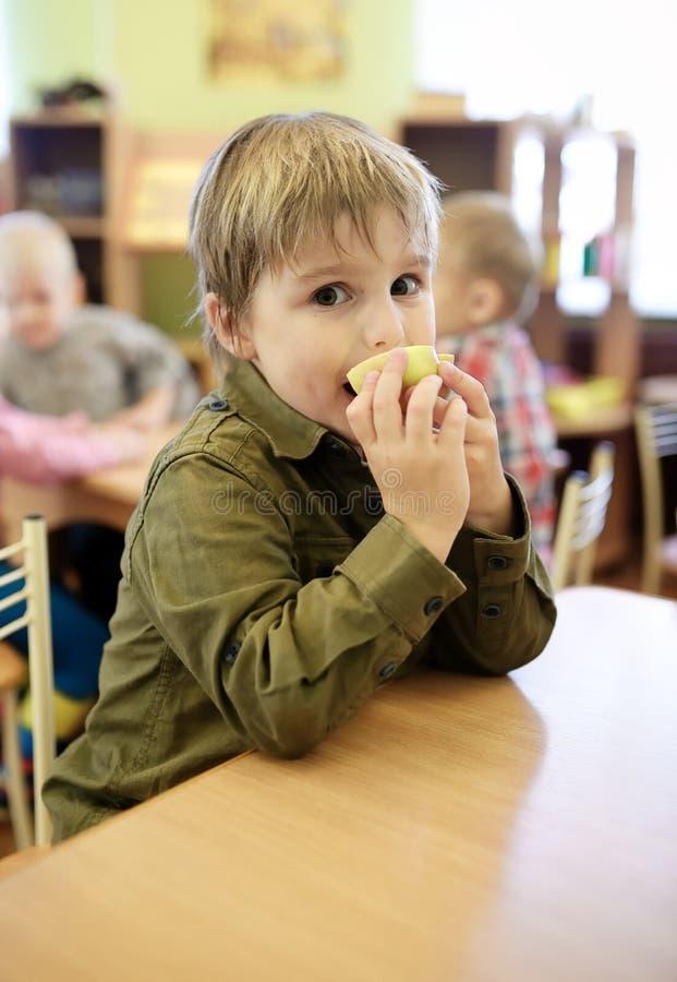 Kinder, die Apfel im Kindergarten essen lizenzfreie stockfotos