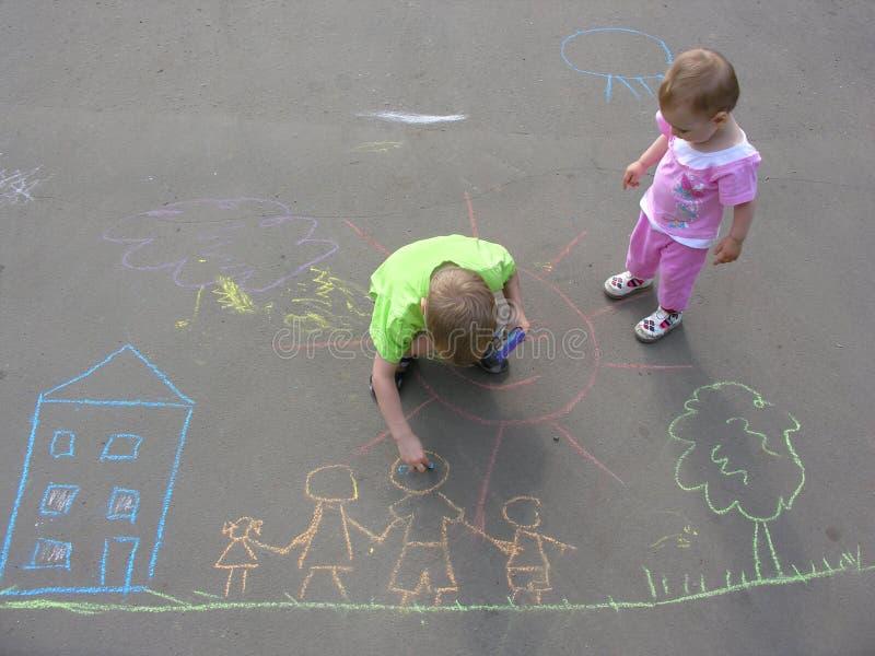 Kinder, die auf Asphalt zeichnen lizenzfreie stockfotos