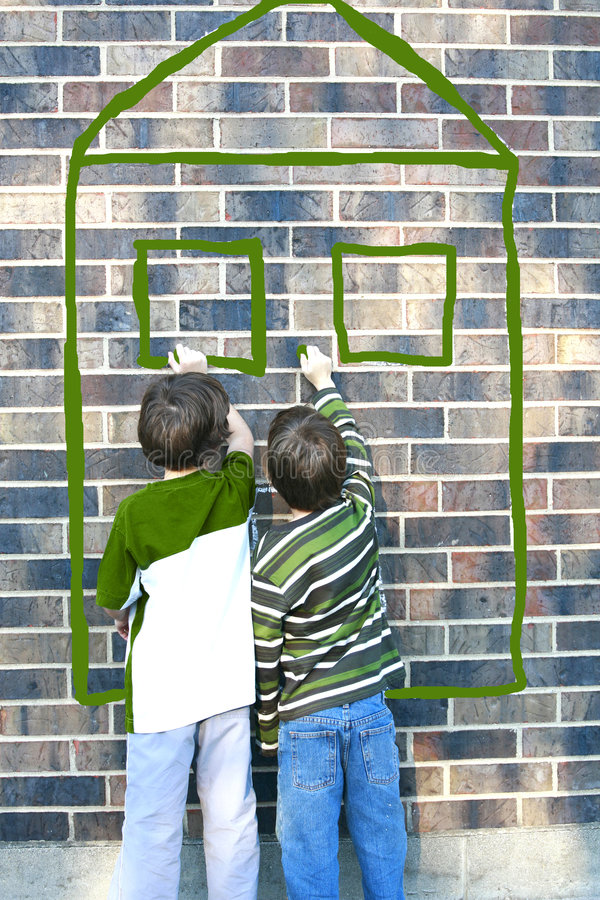 Kinder, die auf Backsteinmauer schreiben stockfotos