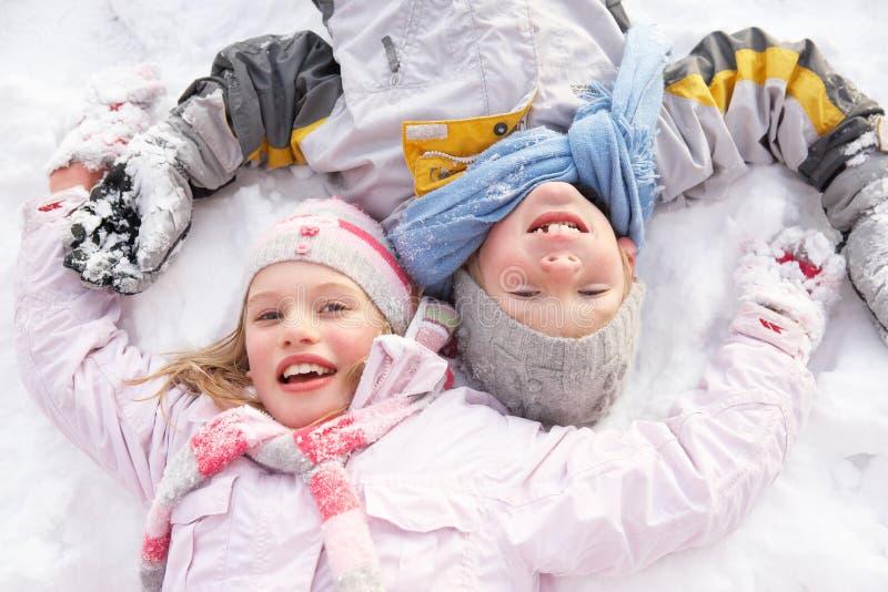Kinder, die auf Boden bildenschnee-Engel legen stockfoto