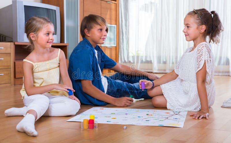 Kinder, die auf Boden mit Spiel sitzen stockfotos