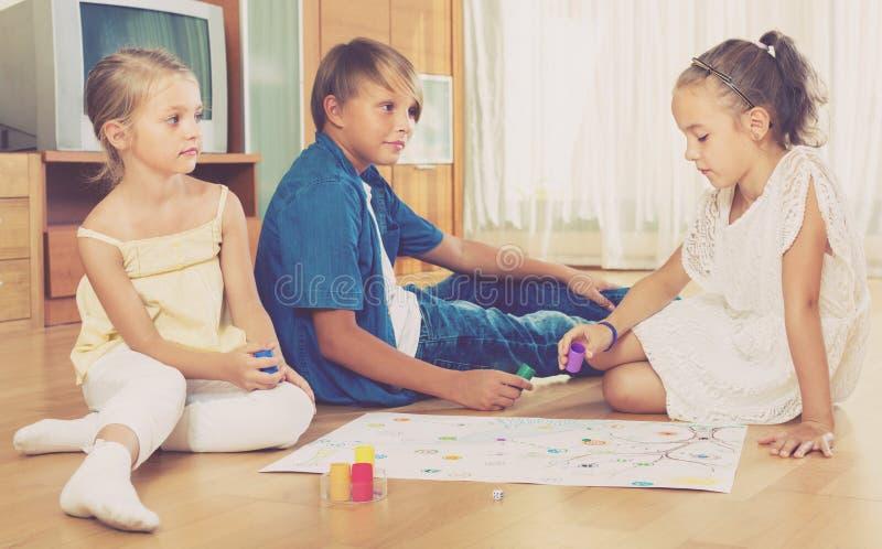 Kinder, die auf Boden mit Spiel sitzen stockfotografie