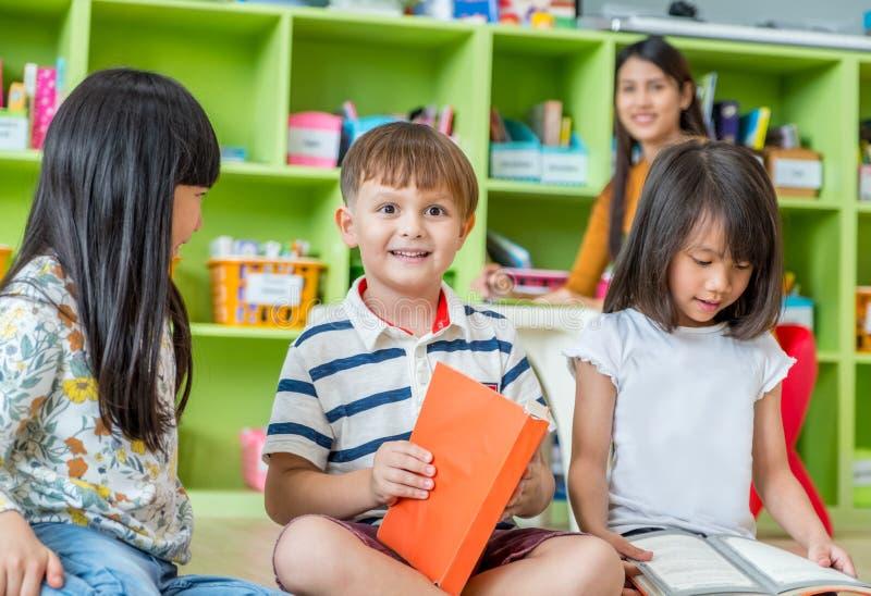 Kinder, die auf Boden sitzen und Geschichtenbuch im Vorschulli lesen stockbild