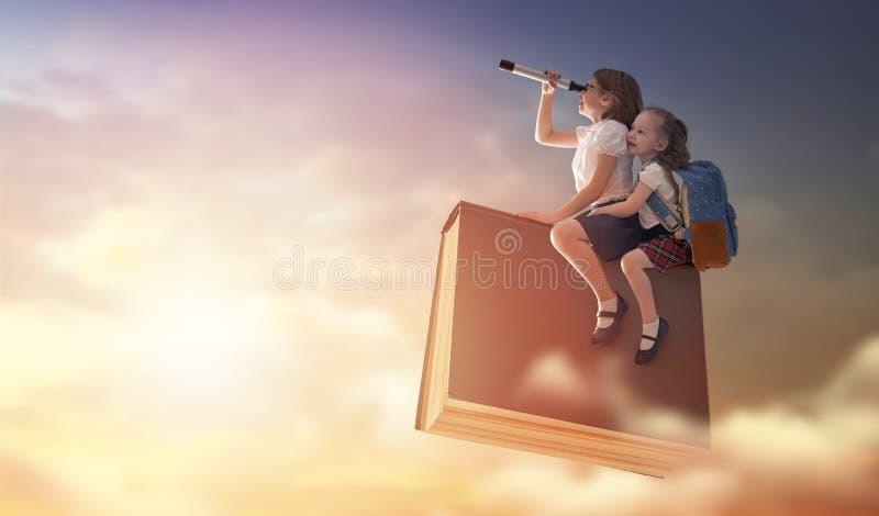 Kinder, die auf das Buch fliegen stockfotos