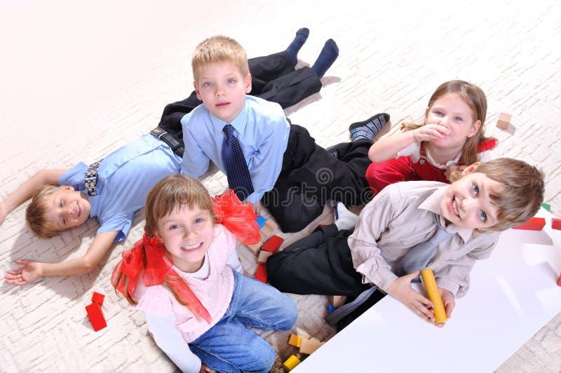 Kinder, die auf dem Fußboden spielen stockfotografie