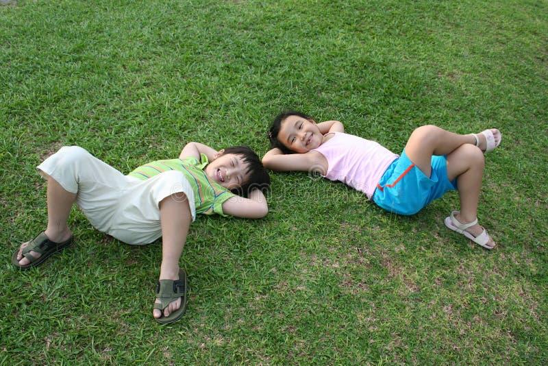 Kinder, die auf dem Gras liegen stockfoto