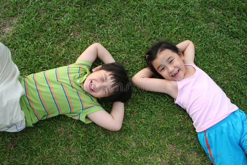Kinder, die auf dem Gras liegen lizenzfreies stockbild