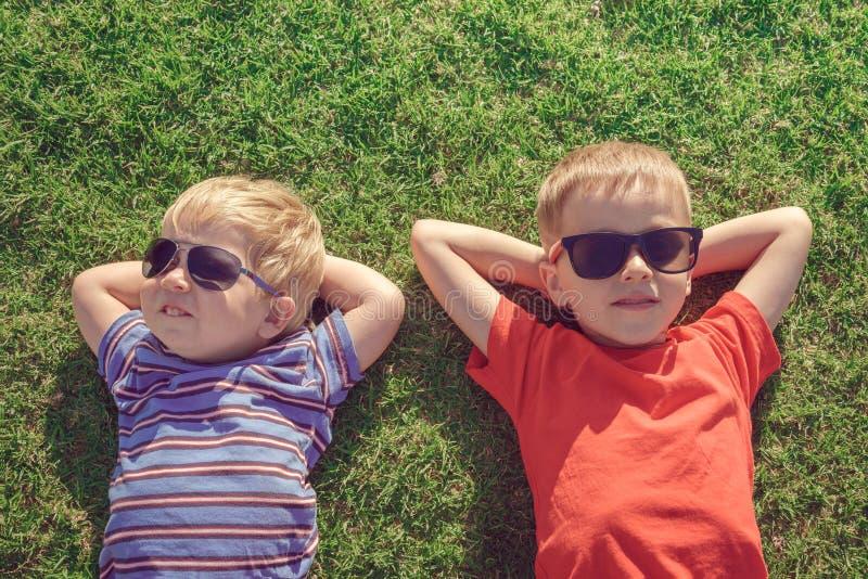 Kinder, die auf dem Gras sich entspannen lizenzfreie stockbilder