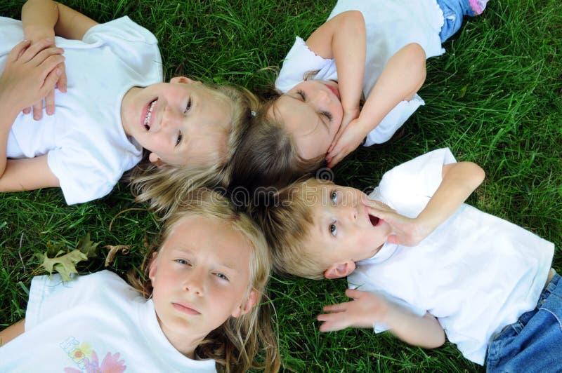 Kinder, die auf dem Gras spielen stockfotografie