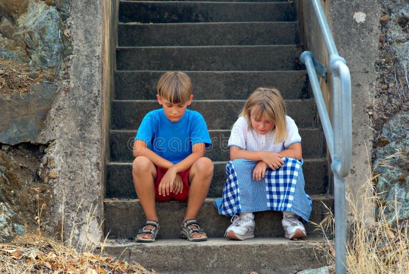 Kinder, die auf den Jobstepps sitzen lizenzfreies stockbild