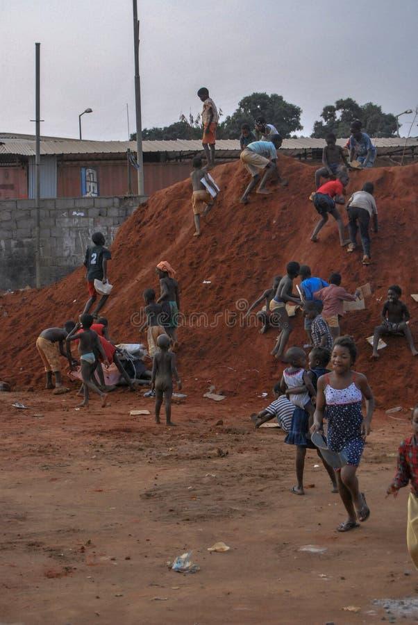 Kinder, die auf einem roten Sandhügel spielen lizenzfreie stockfotos