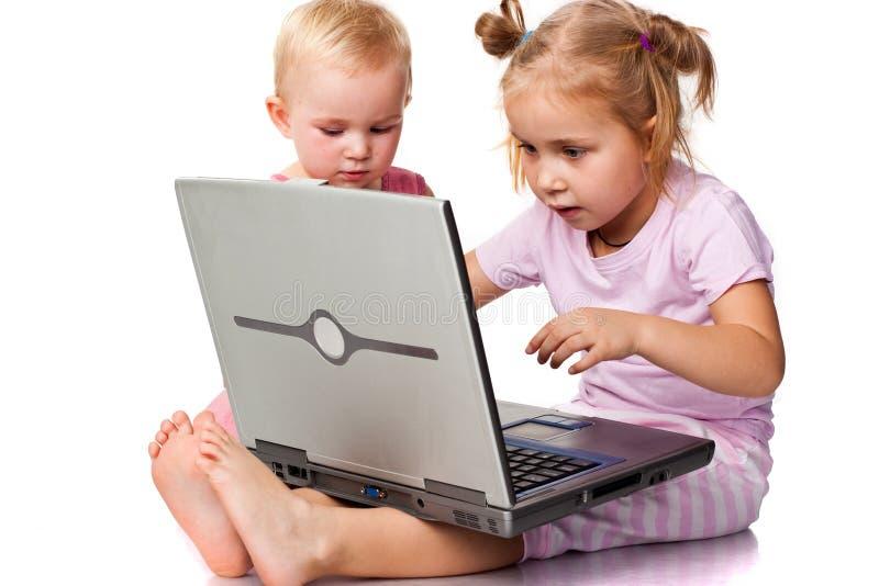 Kinder, die auf Laptop spielen lizenzfreies stockbild