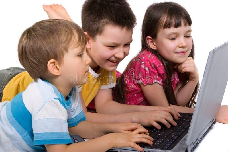 Kinder, die auf Laptop spielen stockfoto