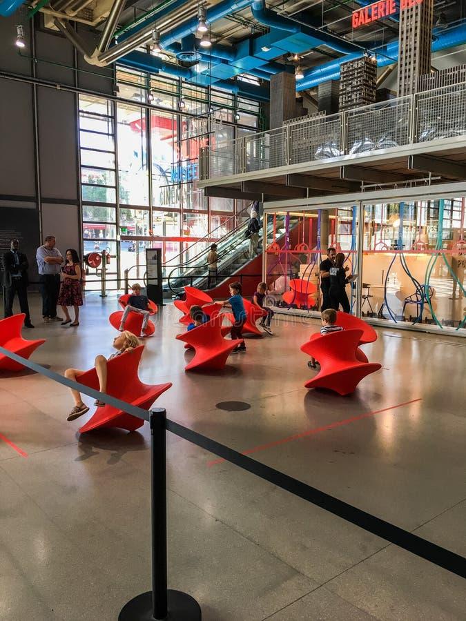 Kinder, die auf orange Spielwaren in der Anzeige in Pompidou-Mitte, Paris, Frankreich schaukeln stockbild