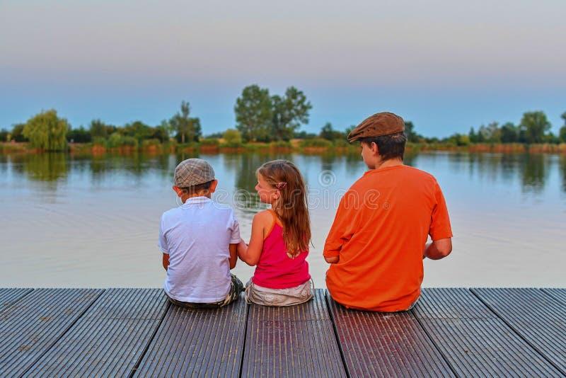 Kinder, die auf Pier sitzen Drei Kinder unterschiedliches Alter - Jugendlichjunge, grundlegender Altersjunge und Vorschule- Mädch stockbild