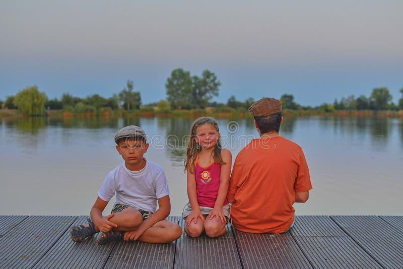 Kinder, die auf Pier sitzen geschwister Drei Kinder unterschiedliches Alter - Jugendlichjunge, grundlegender Altersjunge und Vors stockfoto