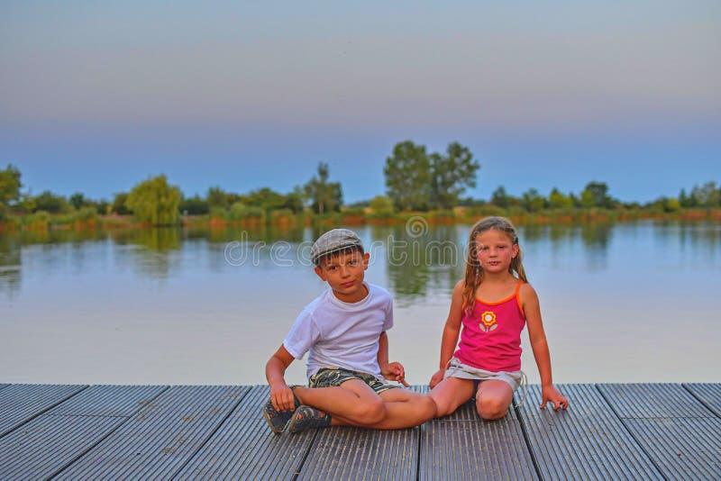 Kinder, die auf Pier sitzen geschwister Zwei Kinder unterschiedliches Alter - grundlegender Altersjunge und Vorschule- Mädchen, d lizenzfreies stockfoto