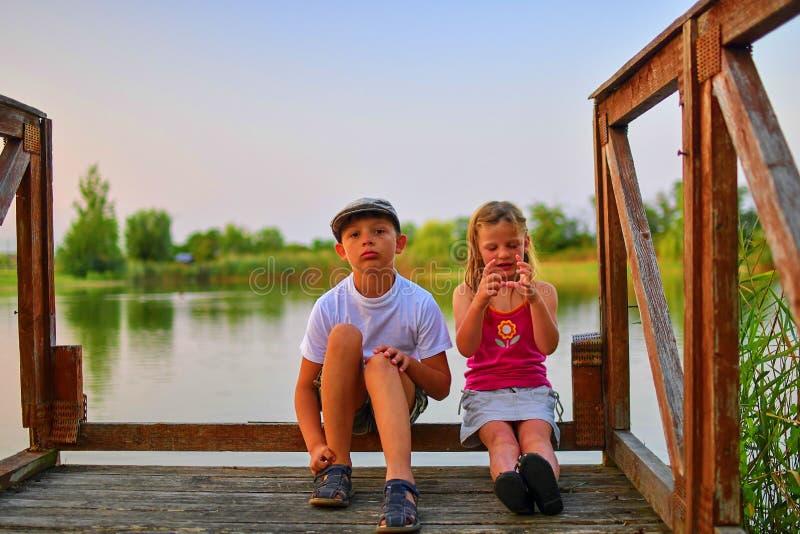 Kinder, die auf Pier sitzen Zwei Kinder unterschiedliches Alter - grundlegender Altersjunge und Vorschule- Mädchen, das auf einem stockbilder
