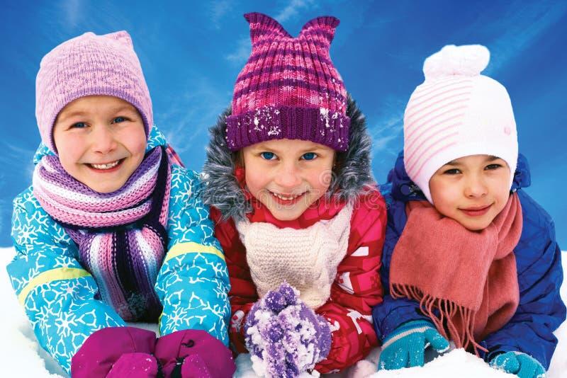 Kinder, die auf Schnee in der Winterzeit spielen lizenzfreie stockfotos