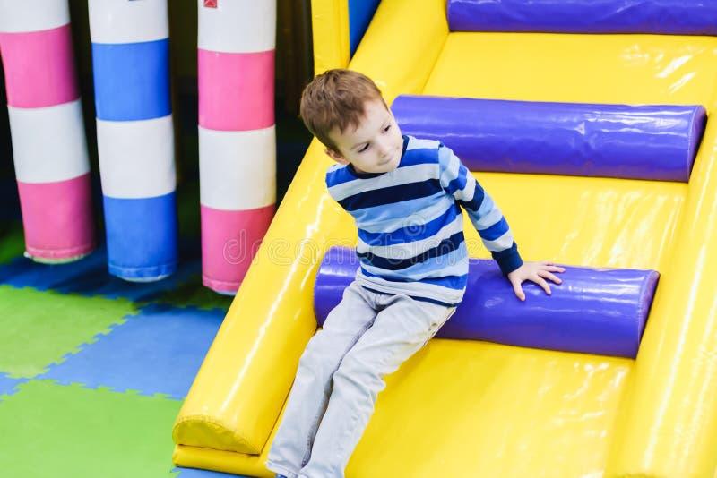 Kinder, die auf Spielplatz im Freien klettern und schieben Kinderspiel im Innenspielplatz Unterhaltungsmitte im Kindergarten oder lizenzfreies stockfoto