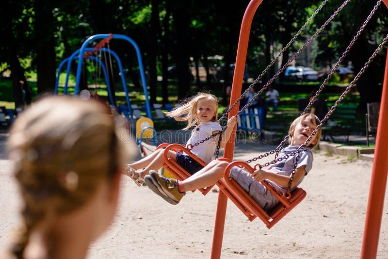 Kinder, die auf Spielplatz schwingen lizenzfreies stockbild