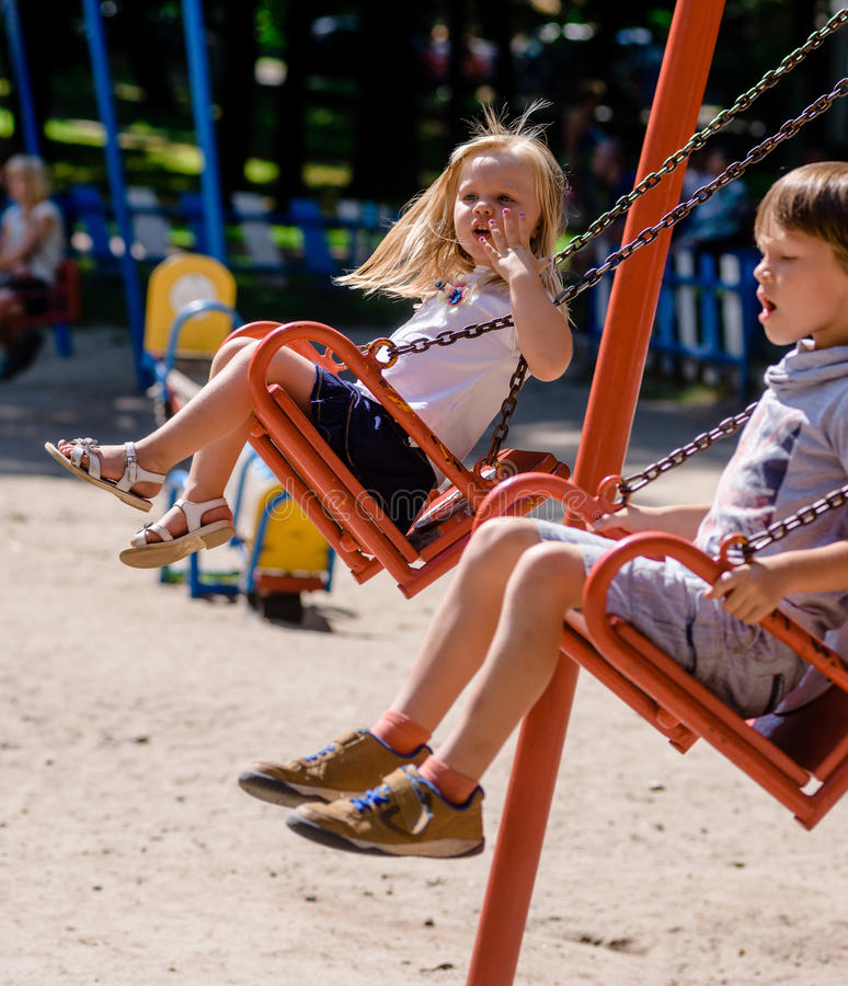 Kinder, die auf Spielplatz schwingen lizenzfreie stockfotos