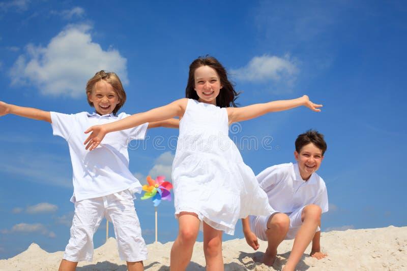 Kinder, die auf Strand spielen stockfoto