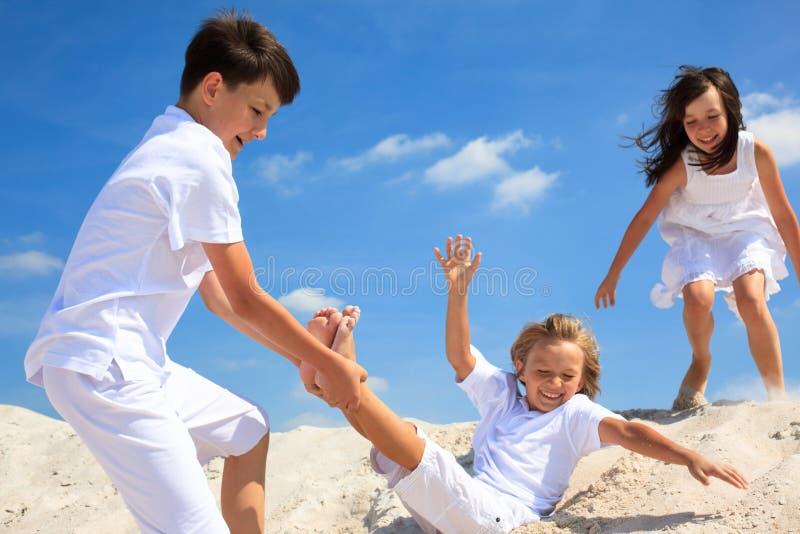 Kinder, die auf Strand spielen stockbild