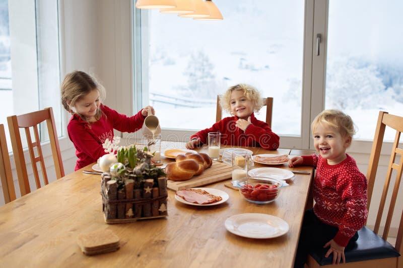 Kinder, die auf Weihnachtsmorgen frühstücken Familie, die zu Hause Brot und Trinkmilch am Tag des verschneiten Winters isst Kinde lizenzfreie stockfotografie